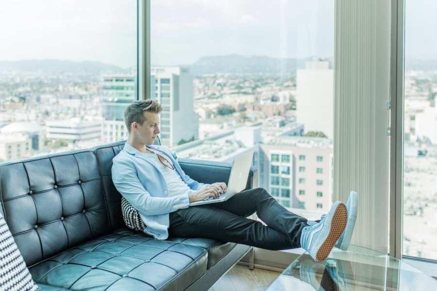 Foto van persoon op bank met laptop op schoot met uitzicht op de stad