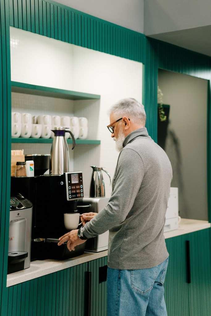 Persoon in zijn eentje bij een koffiemachine